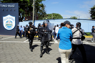 Riot police dislodge journalists from the main entrance of police headquarters in Managua, Nicaragua December 15, 2018