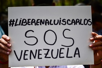 A woman holds a banner that reads 'Free Luis Carlos', outside the Public Prosecutor's office in Caracas, Venezuela, 12 March 2019